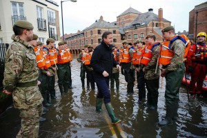 Britain's Prime Minister David Cameron (C) greets British soldiers working on flood relief after the river Ouse burst its banks, in York city centre, northern England, on December 28, 2015. Cameron visited the flood-hit historic city of York on Monday as cities, towns and villages across northern England battled to get back on their feet following devastating storms. AFP PHOTO / POOL / DARREN STAPLES / AFP / DARREN STAPLES (Photo credit should read DARREN STAPLES/AFP/Getty Images)