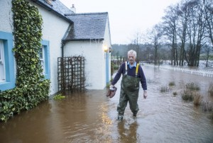 Winter weather Dec 30th 2015. A man holds a pair of shoes as he wades through flood water in Straiton, Scotland, as Storm Frank begins to batter the UK on its way towards flood-hit areas. Picture date: Wednesday December 30, 2015. The latest storm to sweep the country caused widespread disruption in Northern Ireland, with thousands of homes experiencing power cuts. See PA story WEATHER Floods. Photo credit should read: Danny Lawson/PA Wire URN:25129662
